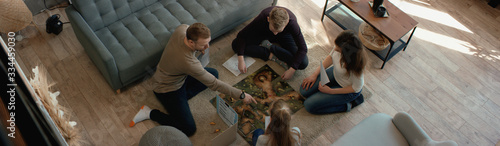 OVERHEAD Family - father, mother and two kids playing a board game together Wallpaper Mural
