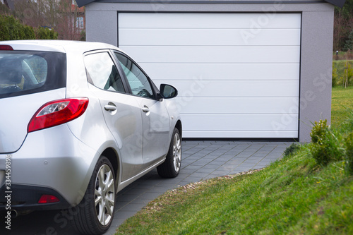 Free-standing garage in the garden with a car parked in front of the gate Wallpaper Mural