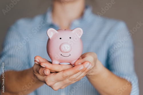 Fototapeta female hands protect pink piggy bank, copy space. Concept of saving money or savings obraz