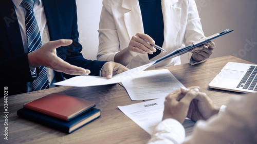 Fototapeta Employer or committee holding reading a resume with talking during about his pro