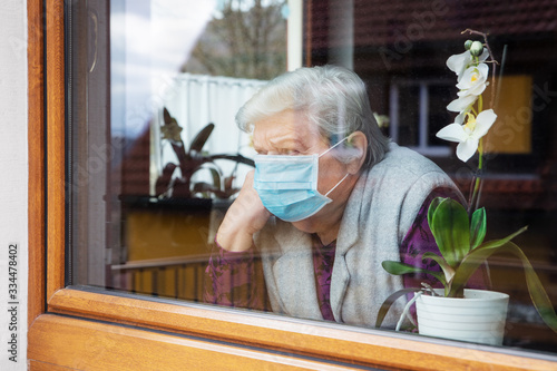 Senior woman with surgical mask sitting on a window at home, coronavirus and cov Fototapete