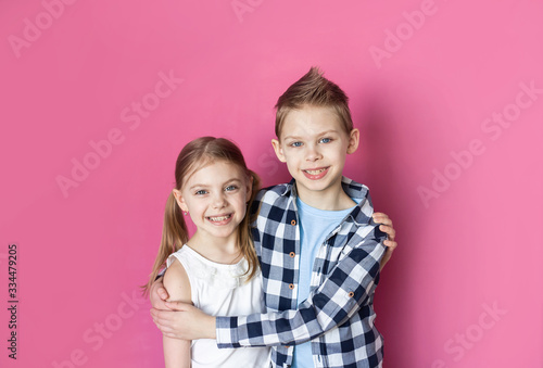 cute children, brother and sister 7-9 years old on a pink background smiling Tablou Canvas