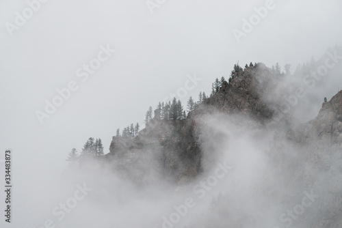 Photo Ghostly alpine view through low clouds to beautiful rockies