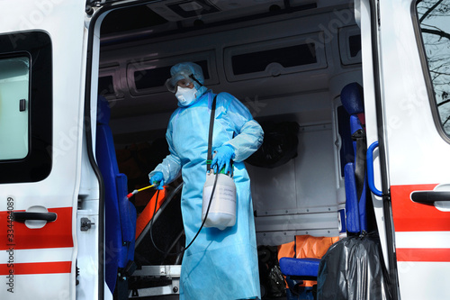 Photo Paramedic in protective mask and costume disinfecting the ambulance car with spr