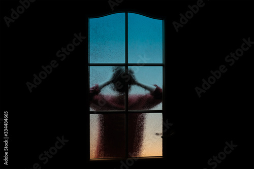 Fotografia Dark silhouette of girl alone in isolation on light background behind closed glass door