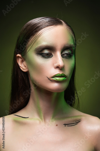 Cuadros en Lienzo A beautiful slim topless girl with avant-garde green makeup close up portrait on a dark background