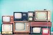 Leinwandbild Motiv Retro classic TV receivers set from circa 60s, 70s and 80s, old wooden television stand with amplifier front mint blue wall background. Broadcasting, news concept. Vintage style filtered photo
