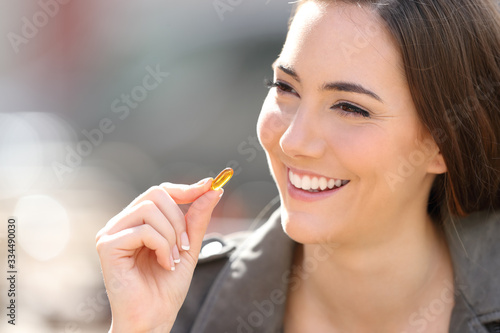 Fototapeta Happy woman taking vitamin pill outdoor obraz