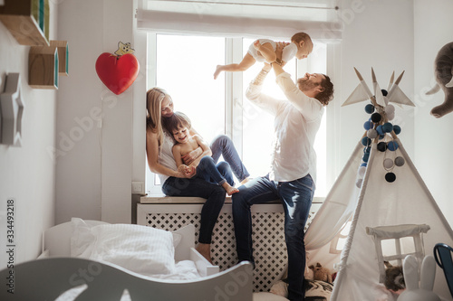 Happy smiling modern caucasian family playing and spending time in a bright white room near the window Fototapete