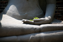 Hands Of Buddha Statue With Green Flowers In Temple Of Thailand.
