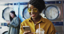 African American Girl Drinking Orange Juice With Straw, Texting Message On Phone And Waiting For Clothes To Get Clean Woman Sipping Drink In Laundry Service Room And Tapping Or Scrolling On Smartphone