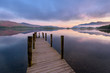 Still Reflections On A Calm Morning With Wooden Jetty In The Lake District, UK.