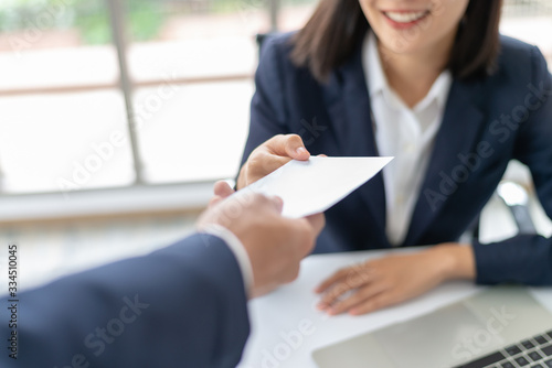 Fototapeta Young Asian business woman receiving salary or bonus money from boss or manager at office happily. obraz