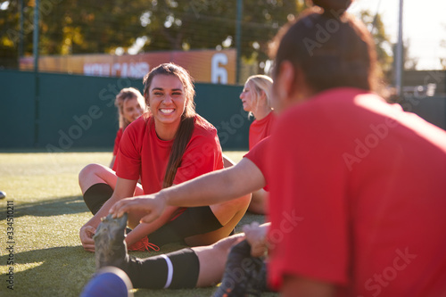 Fototapeta Womens Football Team Stretching Whilst Training For Soccer Match On Outdoor Astro Turf Pitch obraz