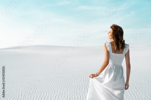 Fotomural back view of beautiful girl in white dress on sandy beach with blue sky