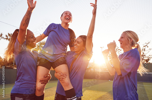Fototapeta Womens Football Team Celebrating Winning Soccer Match Lifting Player Onto Shoulders obraz