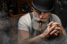 Old Man Smoking A Cigar Indoor...