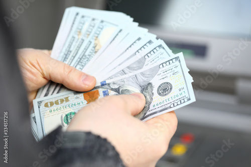Obraz na plátne Male hands holding fantail of hundred dollars banknotes at atm machine