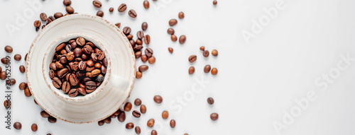 Fototapeta Cup of coffee and coffee beans on a white background with copy space for your text. obraz