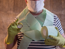 Elderly Man In A Striped T-shirt And Underpants Protect Himself From Entering Market. Blue Mask, Glasses, Gloves, Toilet Paper In Hands. Retired Taught To Make Inexpensive Mask Of Paper And Tape
