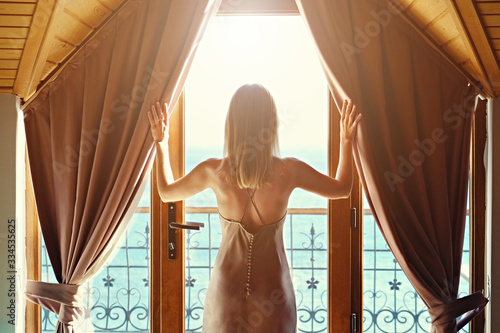 Obraz New day new life concept. Young attractive woman wearing nighties opens curtains of big windows with sea view lets the sunshine in room. Back of fit blonde female in sexy silk nightwear. Background. - fototapety do salonu