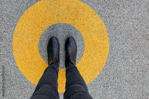 Stampa su Tela Black shoes standing in yellow circle on the asphalt concrete floor