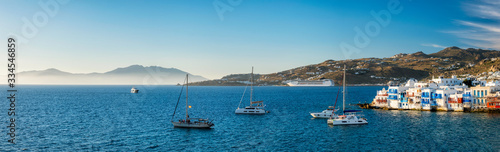 Sunset in Mykonos island, Greece with yachts in the harbor and colorful waterfront houses of Little Venice romantic spot on sunset and cruise ship Canvas Print