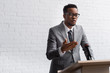 confident african american business speaker on tribune with microphone in conference hall