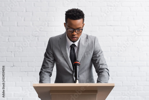 Obraz serious african american business speaker on tribune with microphone in conference hall - fototapety do salonu