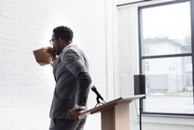 Nervous African American Speaker Breathing With Paper Bag And Having Panic Attack During Business Conference In Office