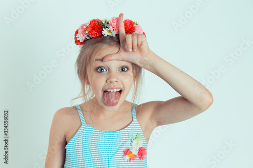 Obraz na plátne kid giving loser sign on forehead with tongue out