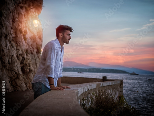 Side view of male in white shirt leaning on border and admiring sea while standi Wallpaper Mural