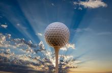 A Golf Ball On A Tee Against The Setting Sun.