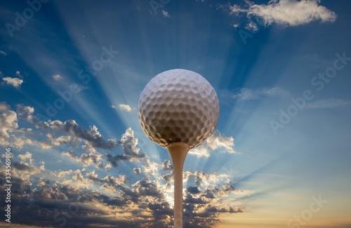 Fotografia A golf ball on a tee against the setting sun.