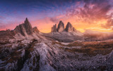 Fototapeta Fototapety z naturą - Mountains and beautiful sky with colorful clouds at sunset Autumn landscape with mountains, stones, grass, trails, blue sky with red and orange clouds. High rocks. Tre Cime in Dolomites, Italy. Travel