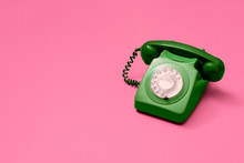 Green Vintage Antique Rotary Phone On A Pink Background With Copy Space And Room For Text With A Right Side Composition.