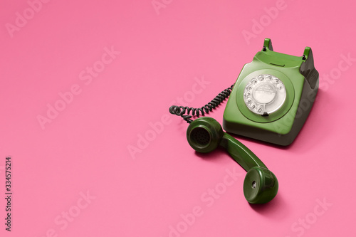 Green vintage antique rotary phone with lifted handset receiver on a pink background with copy space and room for text with a right side composition Canvas Print