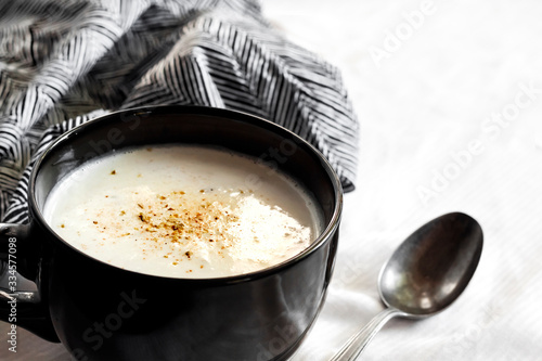 Fotografie, Obraz Cauliflower Soup (Creme du Barry) in black bowl on white background with black a