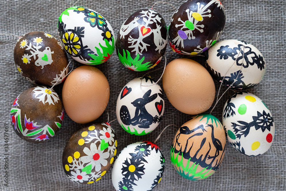 Fototapeta Modern colored Easter eggs according to Lithuanian tradition on a linen fabric background: natural brown, dyed and creatively decorated with figures cut out of paper - bunny, heart, flower, birds