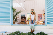 Glamorous Young Woman In Blue Jeans Sitting On Window Sill. Outdoor Shot Of Pretty Long-haired Female Model In Sunglasses And White T-shirt Posing In Summer Day.