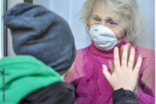 Fotografiet Grandmother in a respiratory mask communicates with her grandson