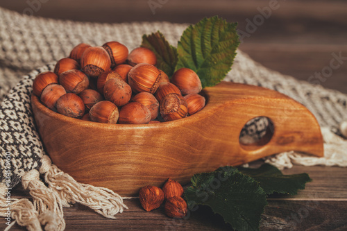 Hazelnuts with leaves in wooden bowl on rustic brown background