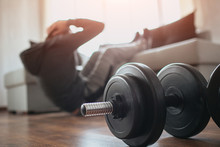 Young Ordinary Man Go In For Sport At Home. Cut View Of A Beginner Or Freshman In Workout Activity At His Apartment. Dumbbells On Pictures Lying On Floor. Trying To Get Better Shape.