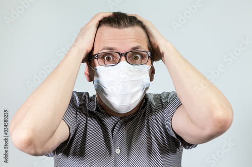 Man buries his head in frustration, wearing medical mask and glasses, grey backg Wallpaper Mural