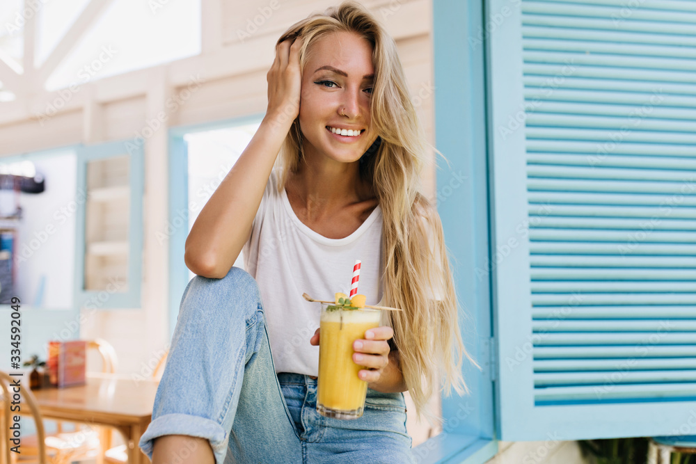 Fototapeta Glamorous long-haired lady drinking cocktail with pleasure. Photo of positive european woman holding glass of cold beverage.