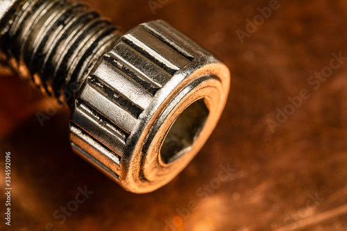 Photo A warm toned macro image of a heavy duty machine thumb screw with an allen wrench hole in the front of it, resting on a worn and oxidized copper work surface