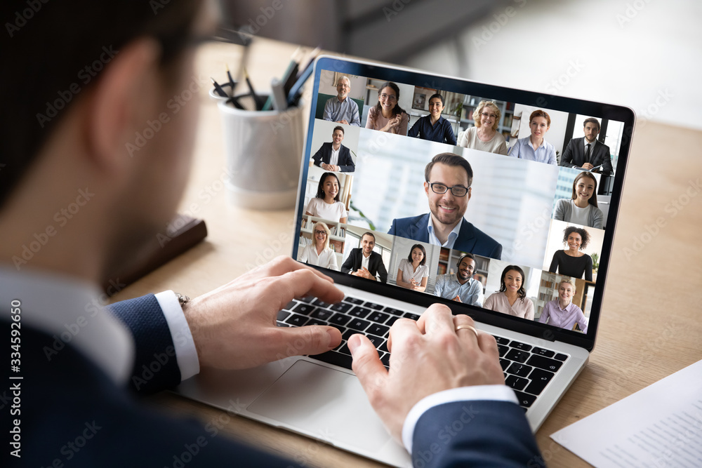 Fototapeta Rear view of businessman speak on web conference with diverse colleagues using laptop Webcam, male employee talk on video call with multiracial coworkers have online meeting briefing from home
