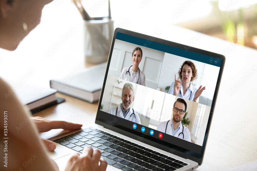 Fototapeta Close up of young female talk on video call consult with diverse doctors colleagues, woman patient have online consultation with GP or physicians, medical nurse in Webcam conference with coworkers