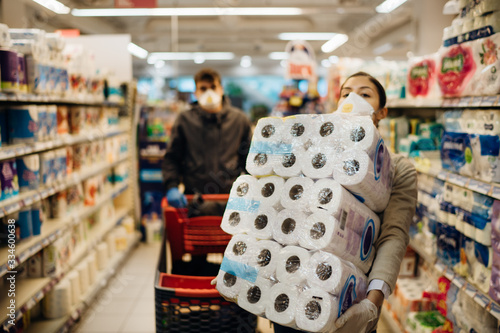 Fotomural Woman couple with mask and gloves panic buying and hoarding toilette paper in supply store