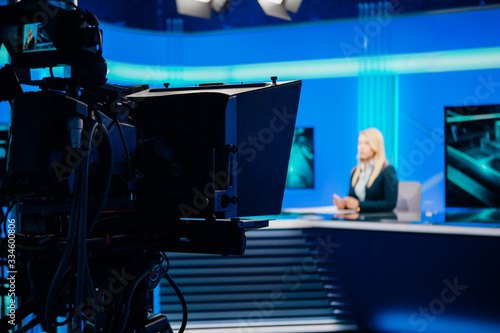 Fotografia Recording at TV news studio positioned camera equipment with television presenter journalist reporting worldwide
